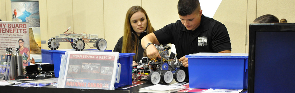 Two ROTC service member assembling a small robot.