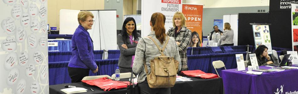 Woman speaking with exhibitors in exhibit hall.