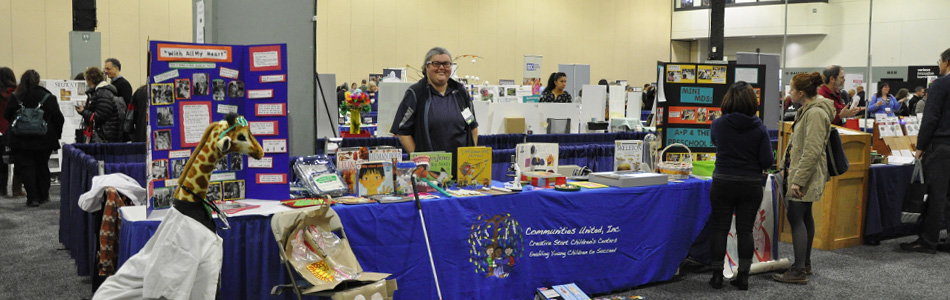 Exhibitor standing at booth.