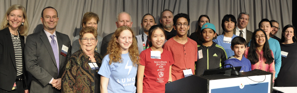 A diverse group of STEM Summit speakers and students on stage.